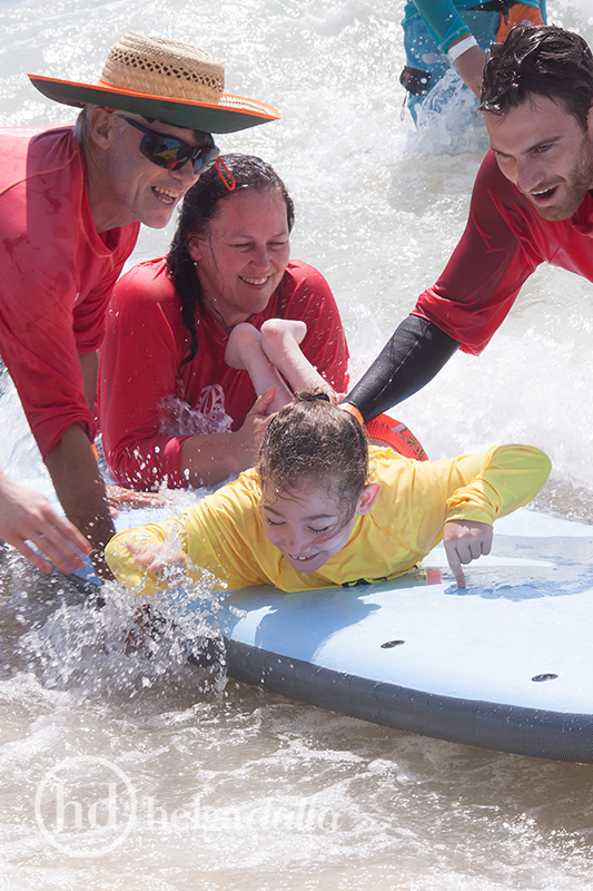 Many helping hands make sure Sophie gets her surfing on.